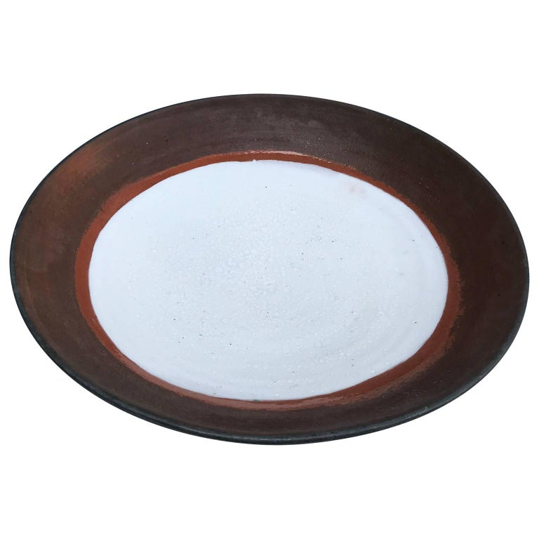 Mid-Century Modern Large Stoneware Charger. This bold charger is signed. It is striking with blue cold-paint on the outside and bottom with white snow-flake glazed inside. A lovely addition to your table for entertaining.