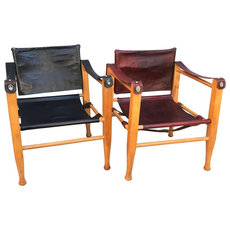 Two vintage Danish Safari chairs, one in thin black leather and one in thin red leather. Both seat has original backing to the leather for strength.