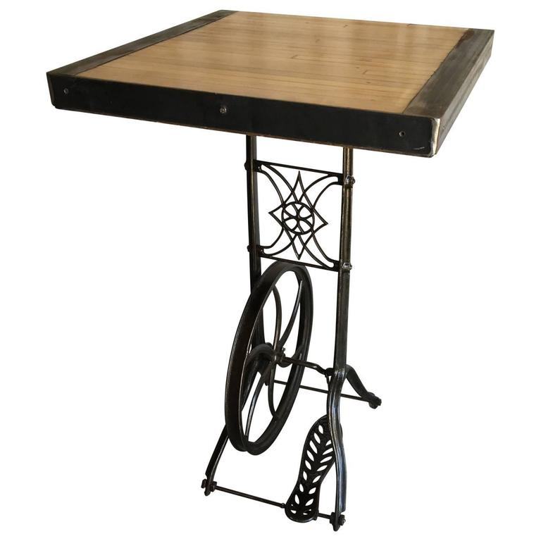 Cafe bar table, made from a Industrial jigsaw wood cutter cast iron base and a steel frames wooden fragment from a old bowling lane.