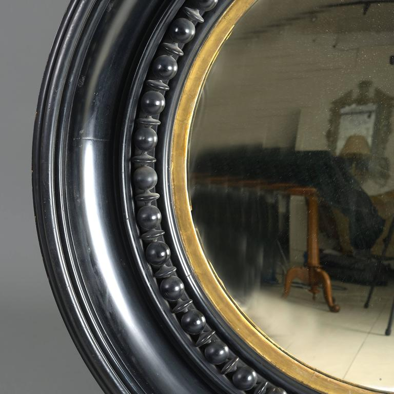 A massive George IV ebonized and parcel-gilt convex mirror, circa 1820.  With original plate in a deep moulded frame with bead-and-reel decoration.  Provenance: Norris Castle, Cowes, Isle of Wight.