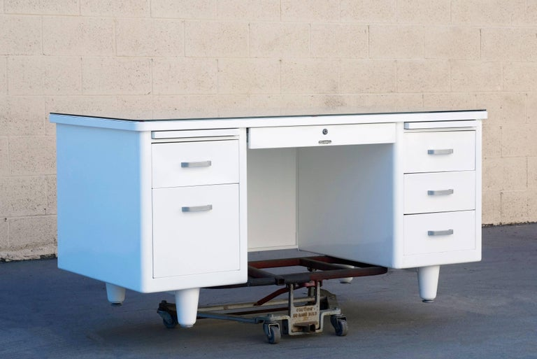 1960s McDowell Craig tanker refinished in gloss white with optional custom glass tabletop. This classic double pedestal desk features many utility drawers, one filing drawer, one locking stationary drawer and two letter trays. All original aluminum