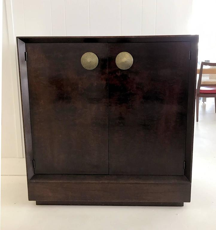 Art Deco cabinet/bookcase designed by Gilbert Rohde in 1940s and manufactured by Herman Miller. Exotic paldao veneer. It has two doors with large bronze gilt pulls and two interior shelves. Stenciled 4108 on the back.