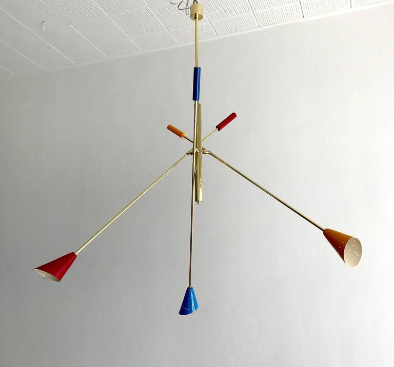 A Mid-Century Italian ceiling light, circa 1950s, in the style of Angelo Lelli. Brass stem with three articulated arms with multicolored shades. Bespoken chandelier in large-scale.  Size is flexible depending on the adjustment of the arm, which