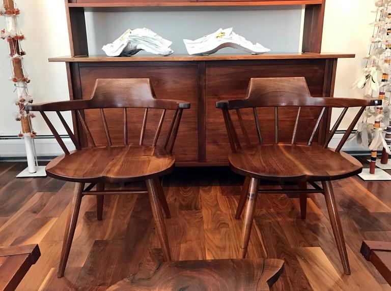 "A wonderful set of four American black Walnut 'Captain"" chairs handcrafted by George Nakashima in his New Hope Studio in 1976. These chairs were designed with creative exposed joints with the backrest extending into the arms. The ergonomic"