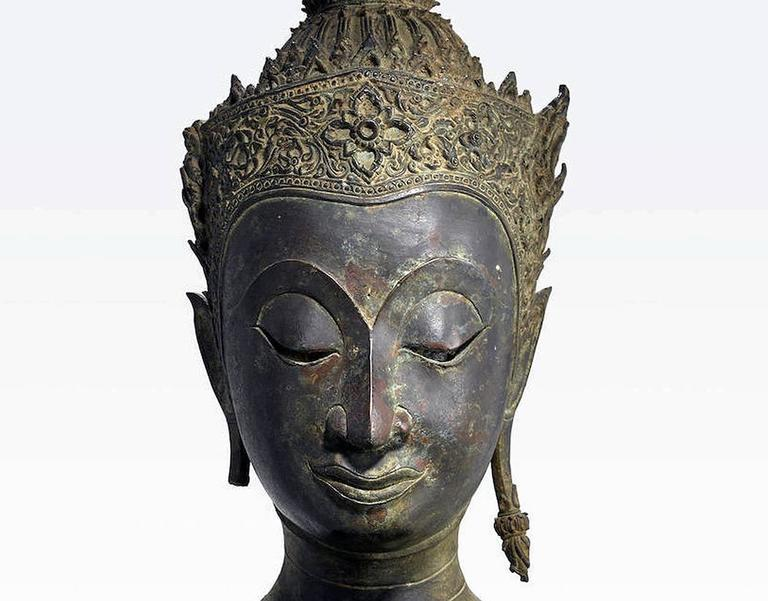 A Thai bronze Buddha head of Ayutthaya Period (1350 to 1767 A.D) on a fitted wood base. The style of this particular Buddha image is dated to the later Ayutthaya period circa 18th century, when it became common to depict Buddha with a lavish royal