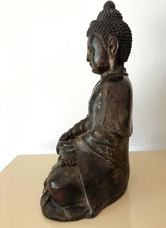 A finely cast bronze statue of Shakyamuni Buddha, the historical Gautama Buddha, in a double-lotus seating position. In Classic Chinese Ming dynasty style and very Fine details in its artistry, this Buddha image exudes the calmness and compassion of