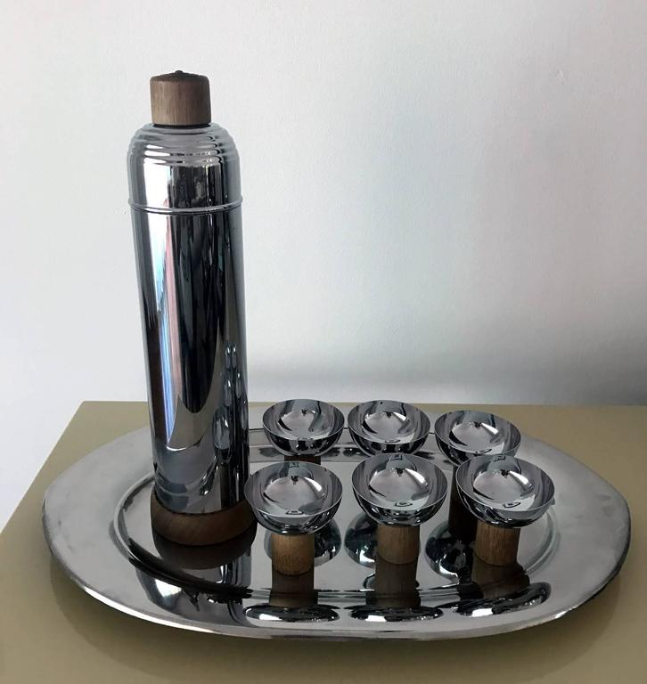 A very cool set of Art Deco style service set from machine age of Japan circa postwar1950s. The chrome set is consist of a carafe with lid, a large tray and six cups with wood accents. The geometrical design is simple and elegant. It has a versatile