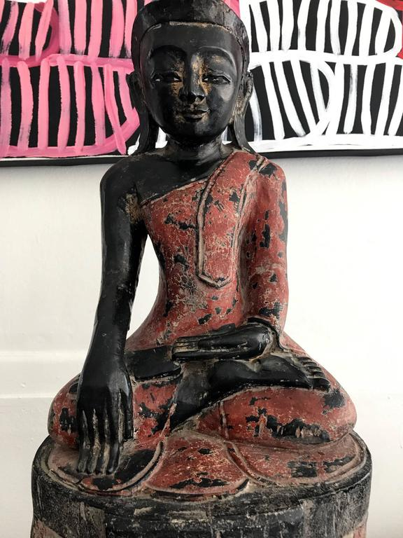 "On offer is a craved wood polychromed Buddha from Burma, Southeast Asia, circa 19th century. The Buddha is seated on an unusual double-lotus throne in an ""adamantine posture"" (vajrasana), with his legs crossed and the soles of both feet"