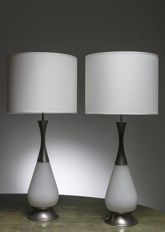 Scarce pair of table lamps by Stilnovo. Huge pieces, with milky glass and aluminium details. Following the Max Ingrand lesson for Fontana Arte, this piece has two-light sources, one inside the glass base and the other on the top.