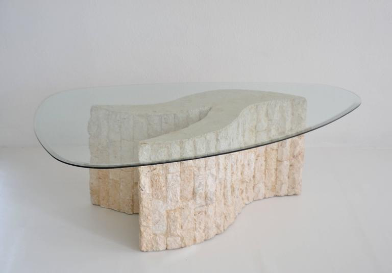 Striking Post-Modern abstract form tessellated marble coffee table, circa 1970s-1980s. This stunning sculptural artisan crafted cocktail table is designed of cut rough hewn stone and accented with an organic boomerang glass top.  Measurements: