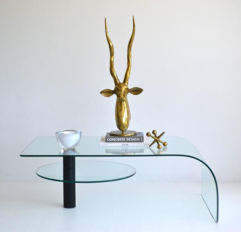 Sculptural Post-Modern two-tier waterfall edge glass cocktail table, circa 1970s - 1980s. This strikingly graphic articulating coffee table is designed with a black powder coated support column with a circular swivel lower tier glass table.  Note: