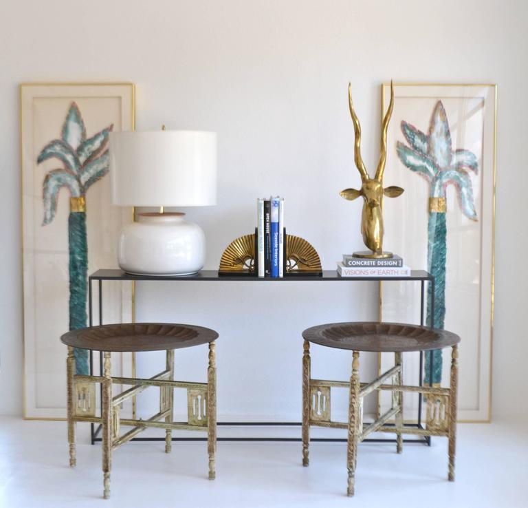 Striking pair of Anglo-Indian brass tray tables, circa 1940s -1950s. These sculptural side tables are designed of etched brass trays on distressed painted hand-carved wooden folding bases. The pair can also be versatilely used as a cocktail or