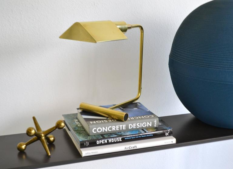 Sculptural midcentury polished brass desk lamp by OMI, circa 1960s-1970s. This architectural table lamp is designed with an articulating shade and a dimmer switch for directional and adjustable lighting. The Koch & Lowy desk lamp is crafted with a