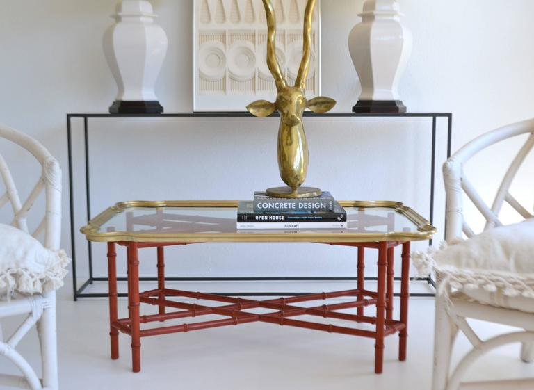Striking Hollywood Regency faux bamboo tray top cocktail table, circa 1950s-1960s. This glamorous coffee table is designed with a polished brass and glass removable tray top mounted on a carved wooden red lacquered stretcher form base.