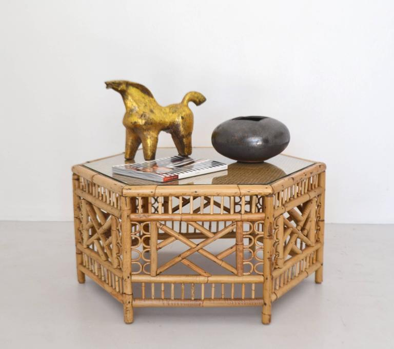Glamorous midcentury bamboo coffee table, circa 1950s-1960s. This striking artisan crafted cocktail table is intricately designed with a bent and cut bamboo hexagonal base and a sturdy wooden and glass top accented with woven cane.