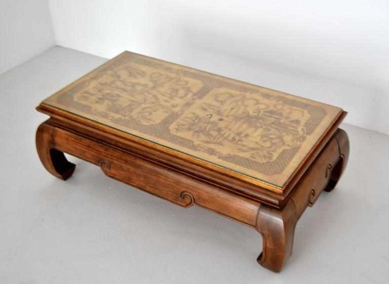 Stunning Hollywood Regency elmwood coffee table, circa 1950s. This striking artisan crafted hardwood cocktail table is designed with a gilt accented chinoiserie inspired hand etched wooden top.