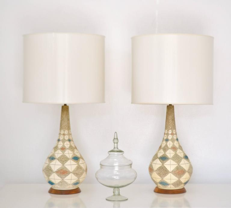 Striking pair of Mid-Century ceramic table lamps, circa 1950s -1960s. These stunning polychrome glazed highly graphic and decorative lamps are mounted on turned walnut bases and wired with brass fittings. Shades not included.  Measurements: 38