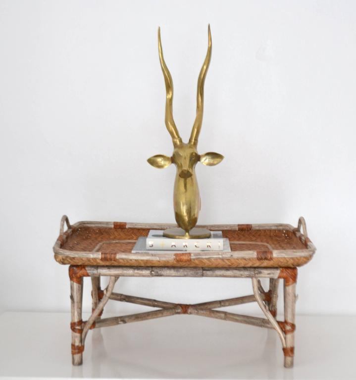 Striking Mid-Century tray top coffee table, circa 1960s-1970s. This stunning artisan crafted cocktail table is designed with a woven rattan tray top mounted on a carved wooden tree limb base with cane wrapped joints. Measurements: 34.75 long x 24.25