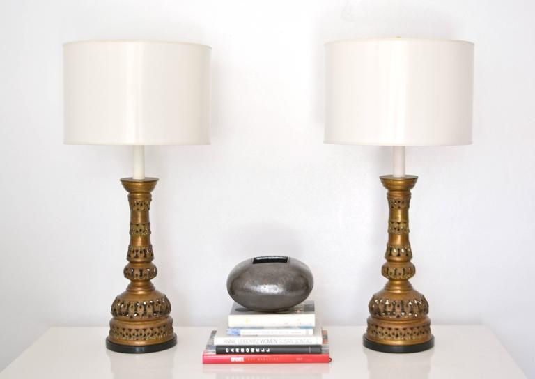 Exquisite pair of midcentury patinated brass candlestick table lamps, circa 1940s-1950s. These stunning table lamps are embellished with an open fretwork design. The brass forms are mounted on turned ebonized wood bases. Shades not