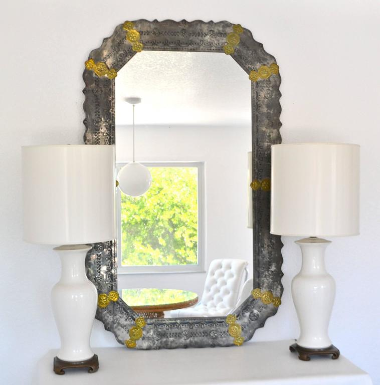 Stunning midcentury etched metal wall mirror, circa 1970s. This striking artisan crafted and highly decorative repousse metal mantel mirror is embellished with brass accents.