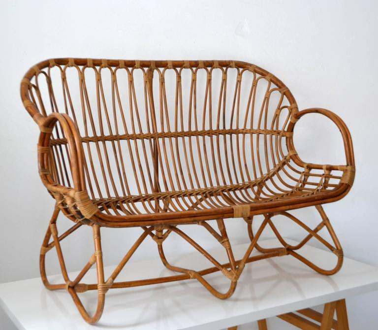 Striking Mid-Century bamboo settee, circa 1960s. This sculptural artisan crafted love seat in the style of Franco Albini is designed of bent bamboo with cane accents.