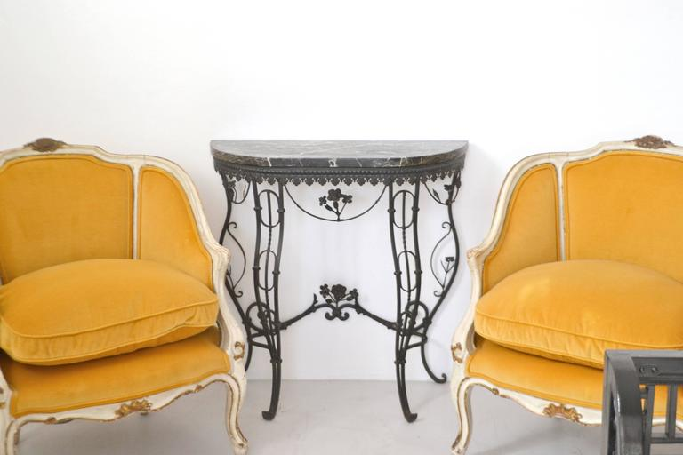 Stunning Hollywood Regency style Italian demilune console table, circa 1950s. This striking artisan crafted hall table is designed of blackened wrought iron with a marble top.