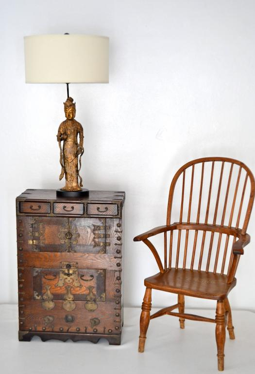 Striking pair of Hollywood Regency Campaign style side tables, circa 1950s. These artisan crafted cabinets / side chests are made of elm and accented with naturally patinated brass hardware. The inside of the nightstands / bedside tables are