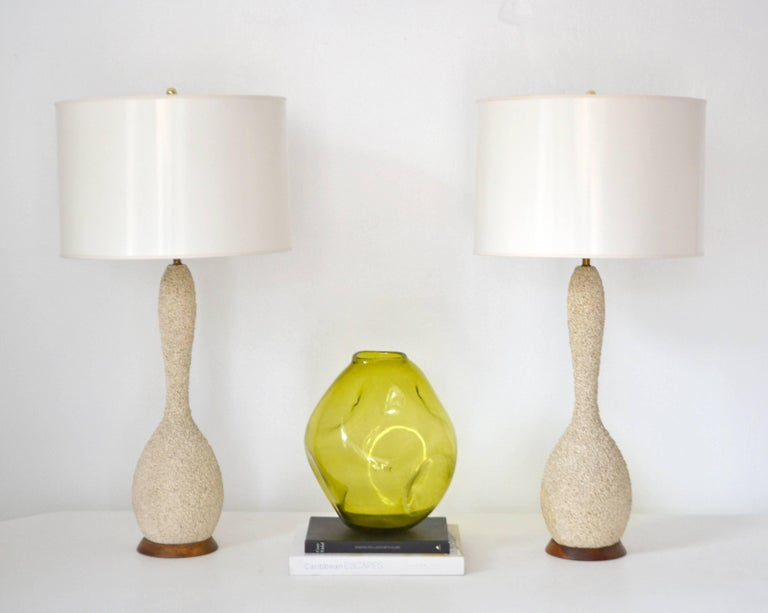 Stunning pair of Mid-Century sand glazed textured ceramic table lamps, circa 1950s-1960s. These artisan crafted hand thrown gourd form table lamps are mounted on turned wood bases and wired with brass fittings. Shades not included.  Measurements: