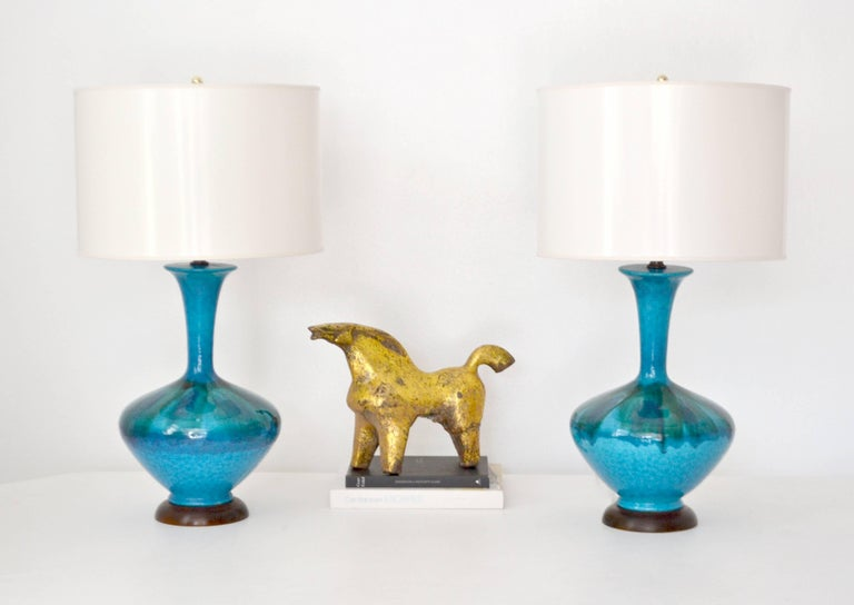 Striking pair of Mid-Century blue green polychrome crackle glazed ceramic jar form table lamps, circa 1950s-1960s. These stunning artisan crafted hand thrown lamps are mounted on turned wood bases and wired with brass fittings. Shades not included.