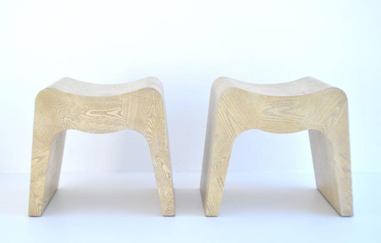 Striking pair of sculptural Postmodern stools, France, 1980s. These custom artisan crafted benches are designed of cerused oak veneer geometrical parquet patterns over molded solid wood forms.
