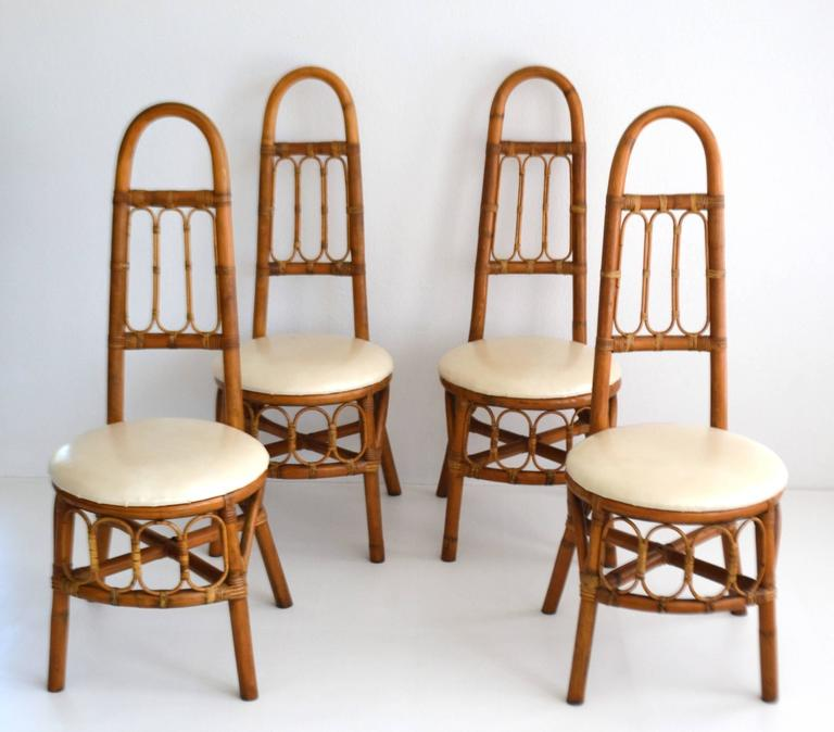 Striking set of four midcentury bent bamboo high back game table chairs, circa 1950s-1960s. These sculptural side chairs/hall chairs are in original excellent condition with a wonderful honey glazed aged patina.