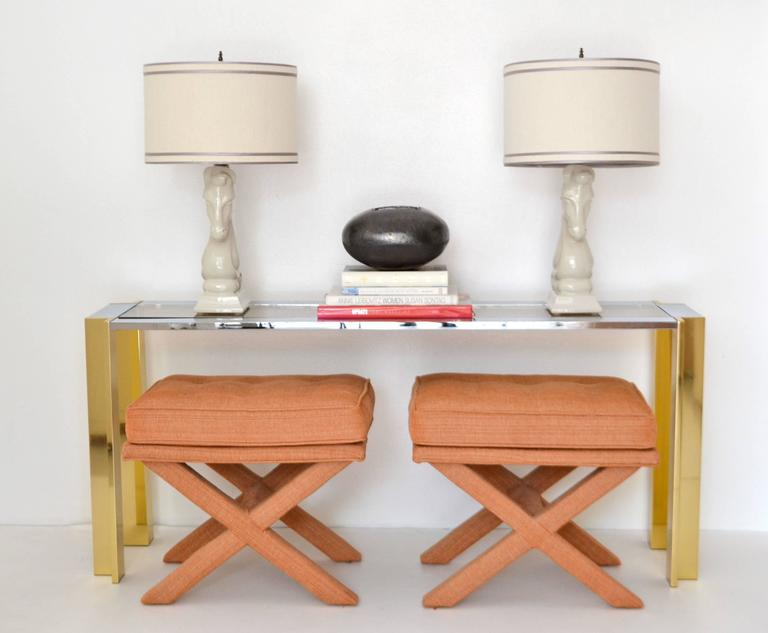 Glamorous pair of Mid-Century X-base button tufted stools, circa 1960s -1970s. These highly decorative benches are upholstered in a cotton linen nubby coral fabric.