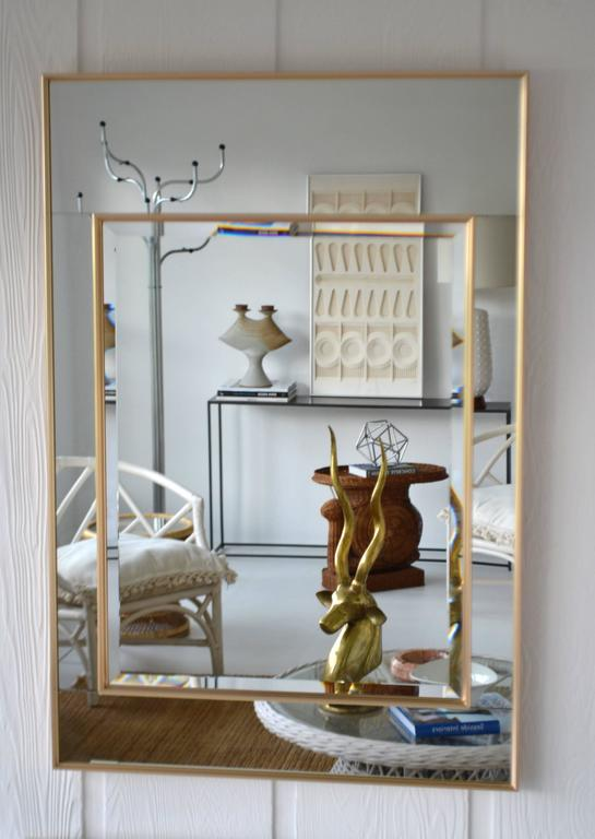 Glamorous Hollywood Regency style wall mirror by La Barge, circa 1980s. This stunning large-scale mirror-framed mantel mirror is designed with mirrored panels encased in reeded brass frames surrounding an inset beveled mirror.