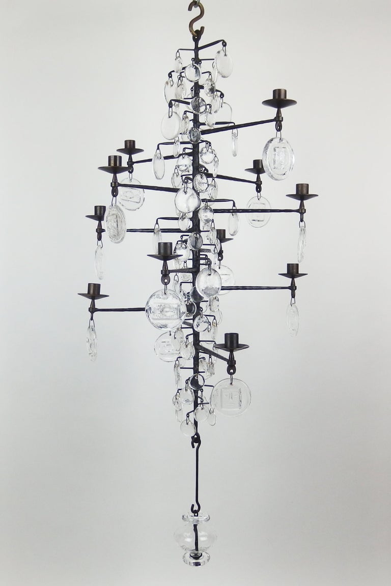A dark grey enameled cast iron candelabra chandelier with 12 arms and 3 sizes glass pendants, the larger pendants with stylized face or fish patterns. Made by Boda Smide for Erik Hoglund.