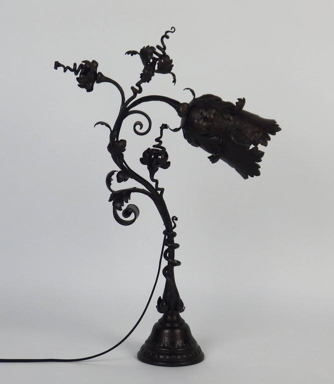 Hammered wrought iron floral table lamp with a black patina. Signed F Marrol