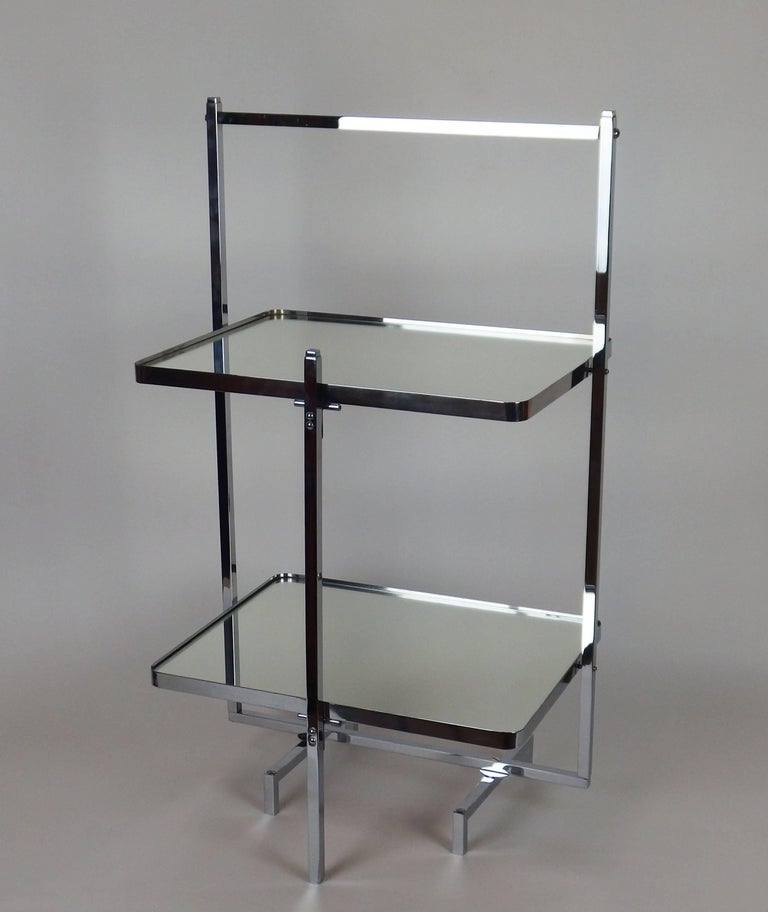 A chromed metal and mirrored glass dessert table with two rectangular trays pivoting on an angular support to fold the table.