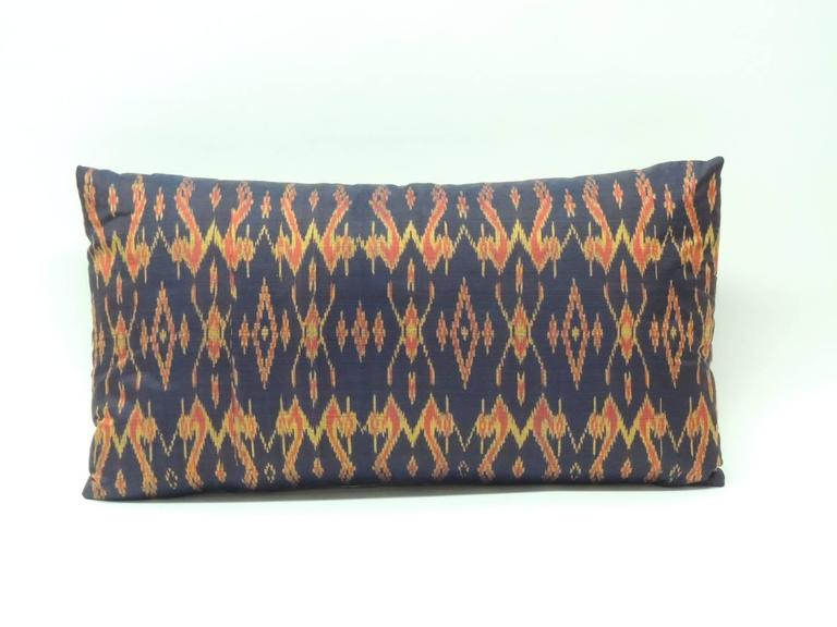 Vintage silk Laos bolster pillow. Traditional tribal pattern in shades of black, red and gold with a satin gray backing.  Decorative pillow handcrafted and designed in the USA. Closure by stitch (no zipper closure) with a custom-made pillow