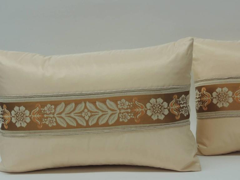These pair of 19th century French silk ribbon lumbar decorative pillows are hand-made by adding a silk woven ribbon onto silk and for embellishment the ribbon has been framed by a peach color vintage silk textile and bordered with an antique silk