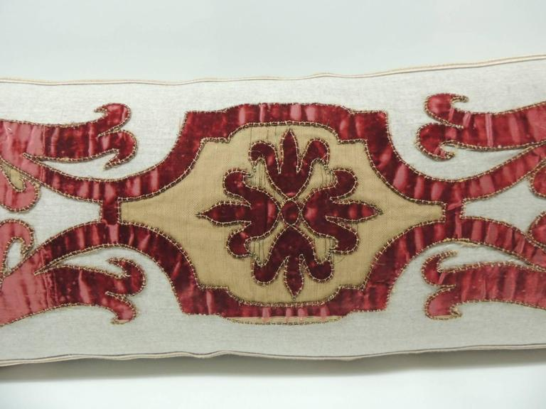 Bolster pillow made with a Byzantine style red cut velvet scrolling appliqué hand-stitched on vintage tan wool. The cut appliqué is a 19th century Italian piece and it was embellished with a gold antique metallic trim. The front panel with the