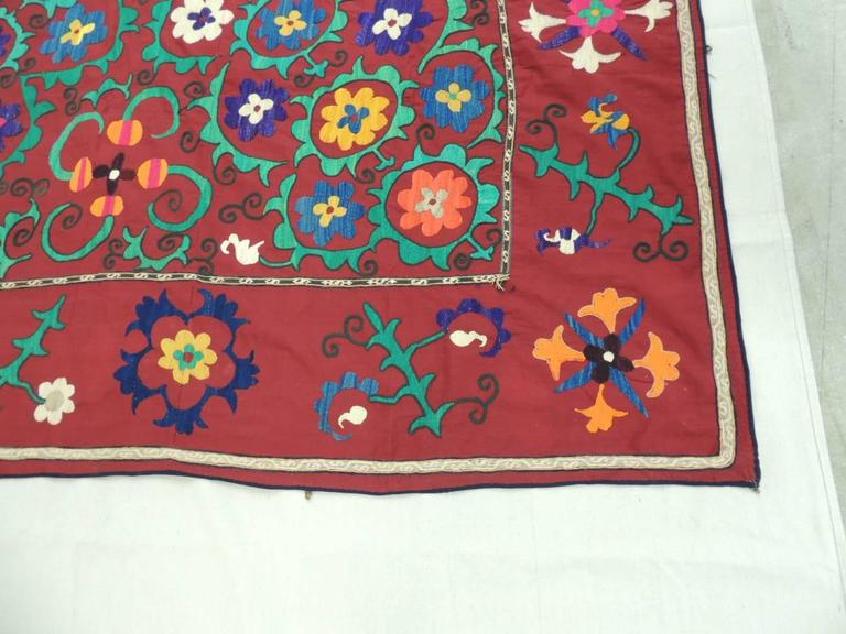 Large vintage colorful hand embroidered Suzani textile. Finished border all around. Great for the back of a sofa or on a table and/or bed cover. In shades of green, blue, red, aqua, white, deep blue, yellow, orange and black, Uzbek, 1960s. Boho chic