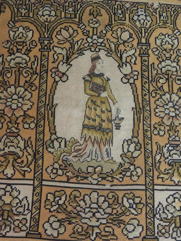English needlework antique tapestry depicting lady in formal wear and hat with book and lantern surrounded by columns and blooming foliage. In the outer body of this tapestry, the woven wool threads are thicker than the ones in the middle. The