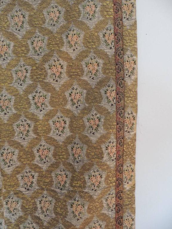 Large antique textile cloth embroidered with gold metallic threads and silk. Framed with an antique embroidered silk on silk floral trim all around the border of the cloth.  Trim is 1.5 inches wide.  No lining on the back of the cloth. An overall