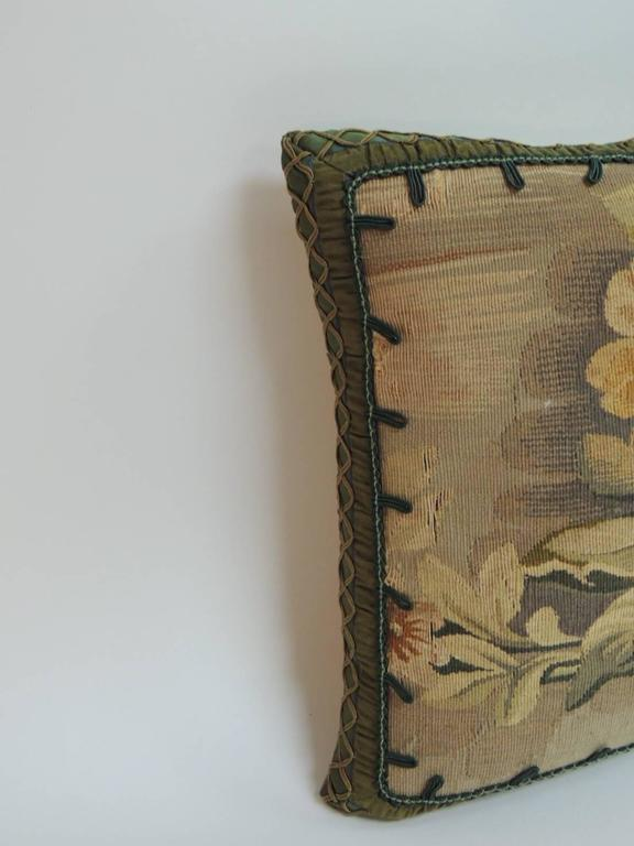 Petite floral Aubusson decorative petite pillow with silk braided trim all around and small hunter green hand-knotted silk decorative trim frames the floral design on the front of the small pillow and tan silk backing. A centuries-old tradition, the
