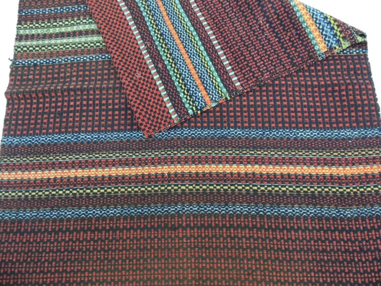 Vintage handwoven Swedish multi-color flat-weaved striped runner Swedish vintage handwoven multi-color flat-weaved striped carpet repurposed as a runner. In colorful shades of red, yellow, blues and natural, Sweden, 1970s. Size: 33 x 90.