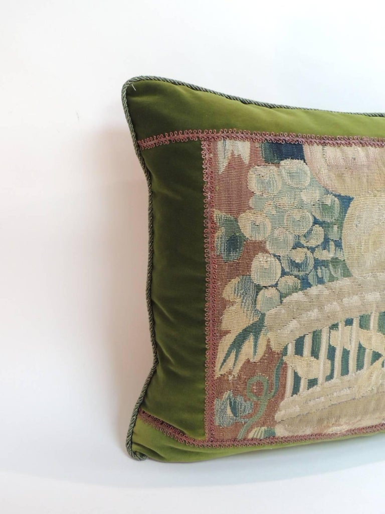 18th century decorative Aubusson tapestry pillow depicting a basket with fruits and flowers framed with hunter green silk velvet, antique copper color metallic trim all around and rope trim at seams. In shades of green, copper, yellow, blue, red,