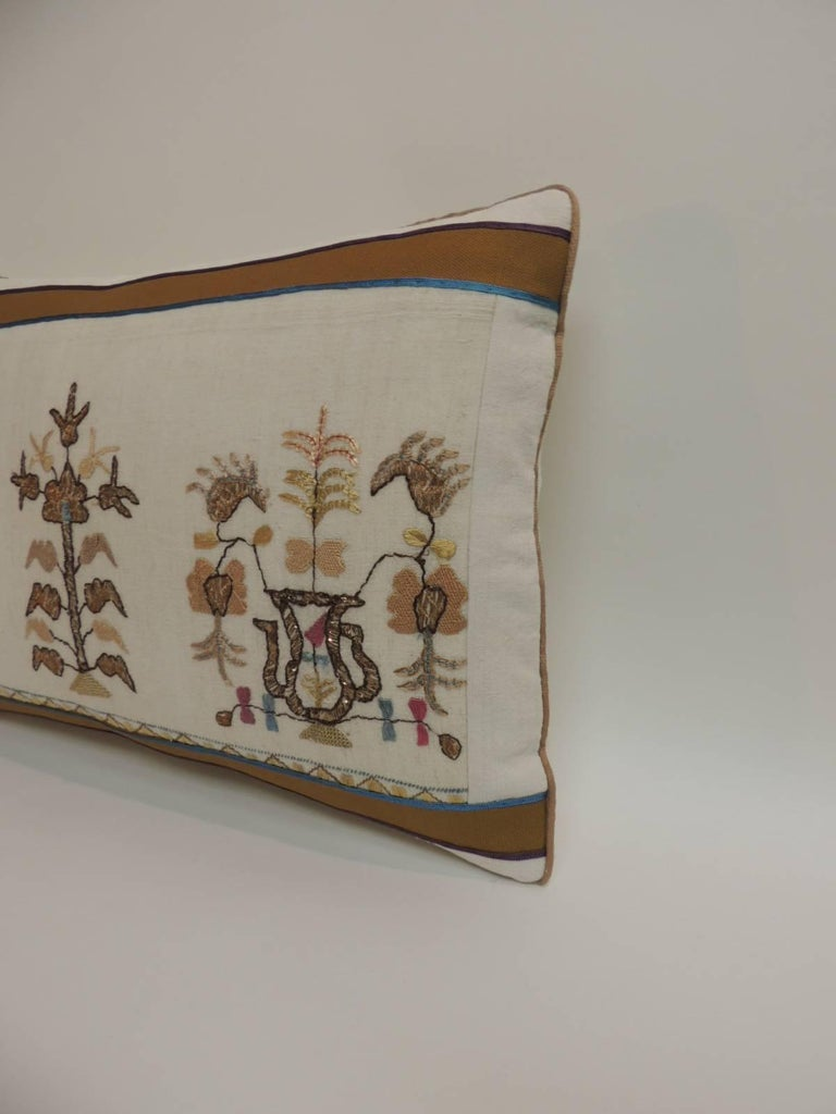 Antique hand-embroidery floral decorative pillow, silk and metallic threads embroidered onto sheer linen. Antique embroidered textile pillow embellished with tan cotton frame featuring small silk trims at seams and tan rope cord all around. In