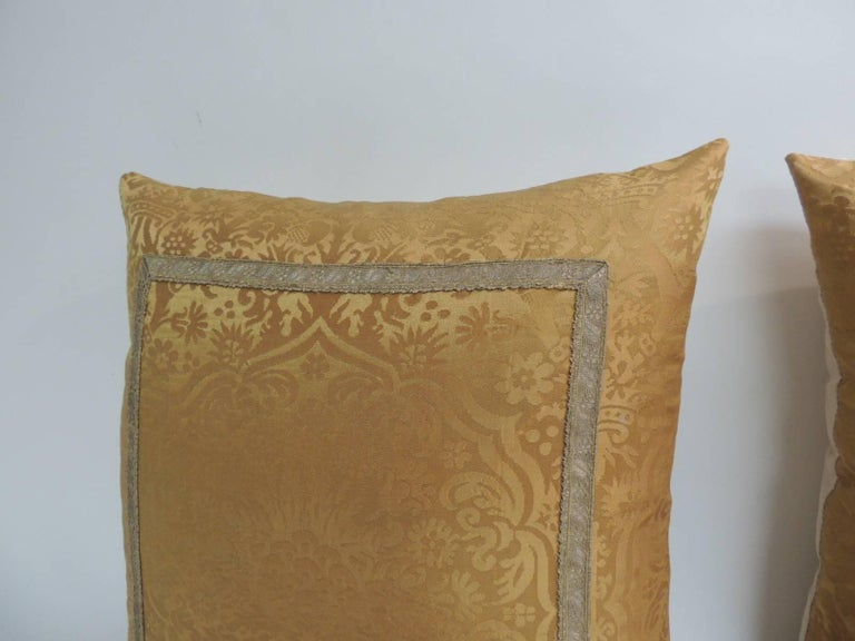 Pair of 19th century silk brocade gold petite square decorative pillows. Pair of 19th century silk brocade gold petite square decorative pillows in yellow tone on tone Damask pattern. Decorative pillows embellished with antique metallic trims and