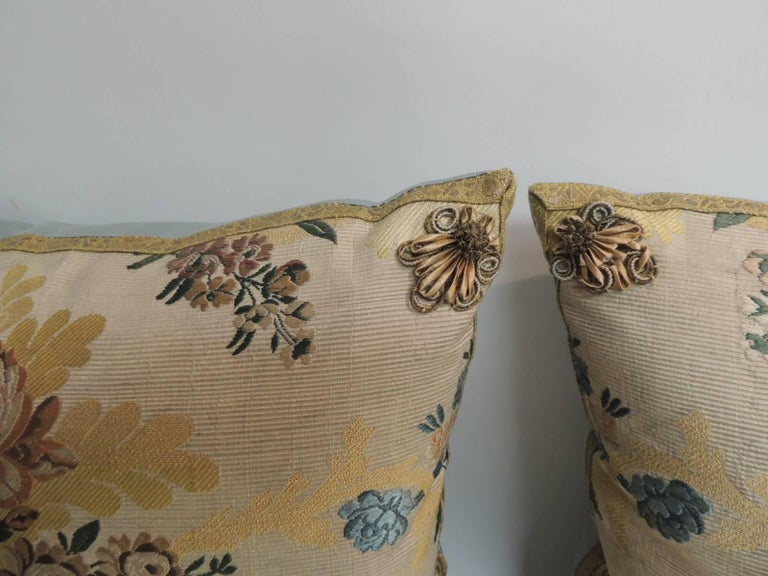 Pair of 19th century French silk Brocade in yellow and blue antique textile decorative pillows. Embellished with gold metallic rosettes on each of the four corners and finished with soft blue silk backings. Antique textile decorative pillows