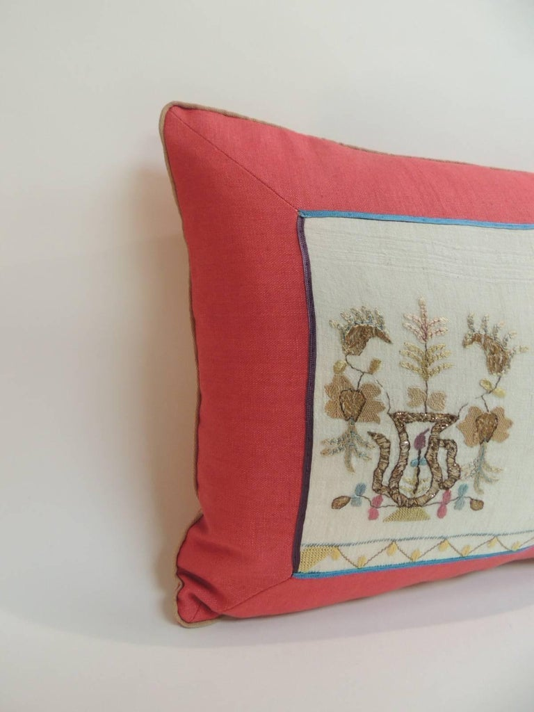 19th century Turkish embroidered linen and silk lumbar decorative pillow Floral pattern of blooming flowers embroidered on linen with copper metallic threads. Accentuated with a flat silk trims and red linen frame and backing. In shades of blue,