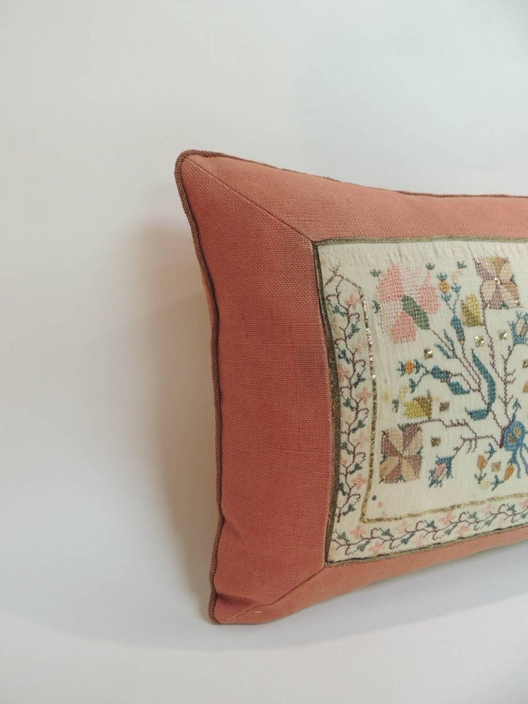 19th century Turkish embroidered linen and silk decorative lumbar pillow Hand-made with a floral pattern embroidered silk on linen textile with gold metallic thread accents. Lumbar decorative pillow framed with an orange linen and orange trims.